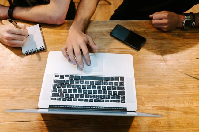 Dall'alto di coltura baristi maschili seduti al bancone di legno in caffetteria e lavorare insieme durante l'utilizzo di laptop e prendere appunti nel quaderno — Foto stock