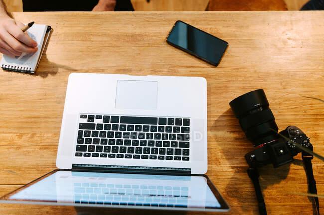 Desde arriba de la cosecha baristas masculinos sentados en el mostrador de madera en la cafetería y trabajando juntos mientras se utiliza el ordenador portátil y tomar notas en el cuaderno - foto de stock