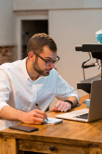 Focused male barista sitting at wooden counter with laptop and taking notes in notebook while working in coffee shop — Stock Photo