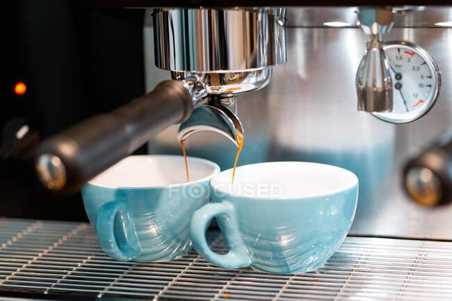 Професійна кавова машина наливає каву в маленькі керамічні чашки в кав