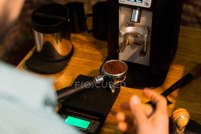 Crop unrecognizable barista pressing coffee in portafilter with tamper while preparing beverage in cafe — Stock Photo