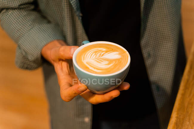 High angle of faceless crop male barista standing with cup of cappuccino with coffee art on froth — Stock Photo