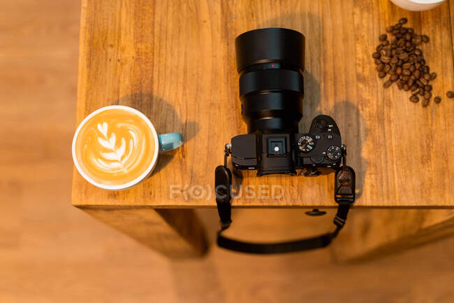 From above of cup of cappuccino with art on foam and professional photo camera placed on wooden table with coffee beans in cafe — Stock Photo