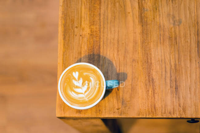 Top view of mug of cappuccino with coffee art on foam placed on wooden table in cafe — Stock Photo