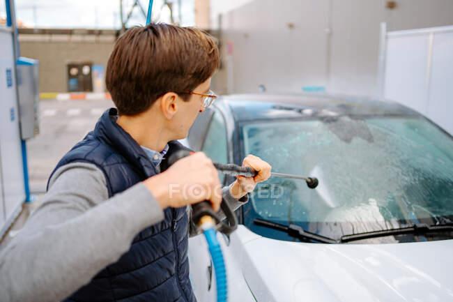 Сконцентрований молодий чоловік у повсякденному одязі, окуляри миють вітрове скло автомобіля з водяним пістолетом на вулиці. — стокове фото