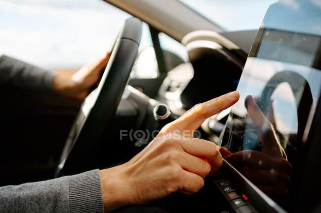 Вид сбоку неузнаваемого мужчины-водителя в повседневной одежде на сенсорный экран GPS-навигатора, сидящего в современном автомобиле в солнечный день — стоковое фото