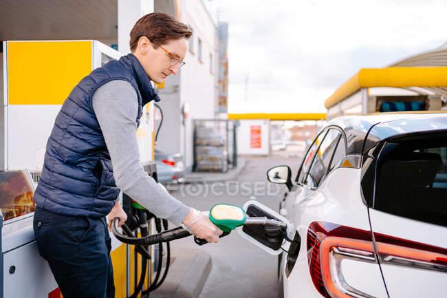 Vue latérale du jeune homme sérieux en vêtements décontractés et lunettes avec des gants en plastique remplissant le carburant dans la voiture moderne dans la station-service en journée — Photo de stock