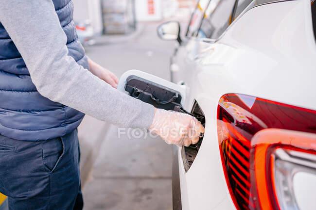 Vue latérale de l'homme recadré méconnaissable avec des gants en plastique remplissant le carburant dans la voiture moderne dans la station-service de jour — Photo de stock