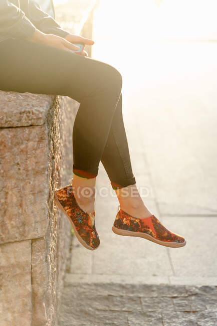 Crop legs of slim female wearing jeans and summer colorful unusual footwear relaxing on city street — Stock Photo