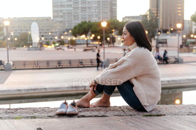 Vista lateral de la tierna y tranquila hembra abrazando las rodillas mientras está sentada en el terraplén de piedra en la ciudad por la noche y mirando hacia otro lado - foto de stock