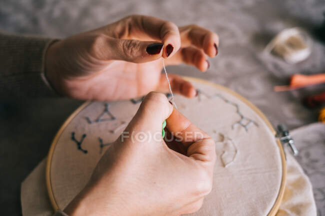 From above crop female with hoop and threads embroidering star constellations while sitting at table in light workshop — Stock Photo