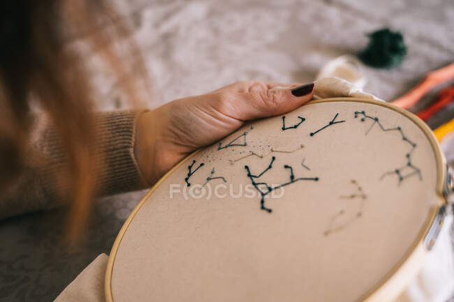 Side view of crop female with hoop and threads embroidering star constellations while sitting at table in light workshop — Stock Photo