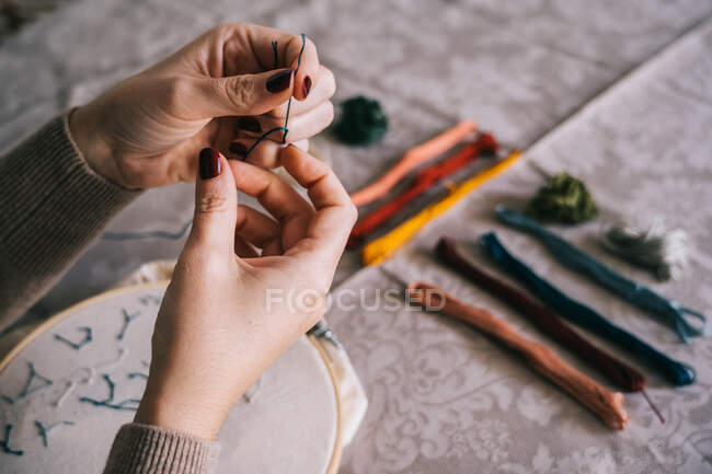 Crop anonymous female with manicured hands threading needle while sitting at table with threads and hoop and doing embroidery — Stock Photo