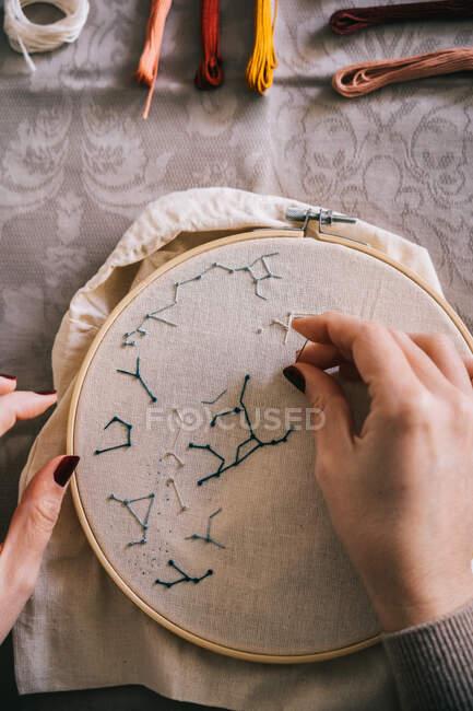 Из выше урожая женщина с обручем и нитками вышивки звездных созвездий, сидя за столом в легкой мастерской — стоковое фото