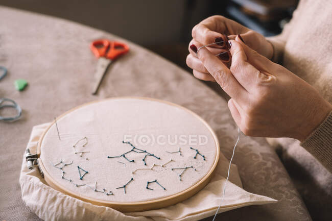 Crop anonymous female in casual outfit threading needle for sewing work while sitting at table in light studio — Stock Photo