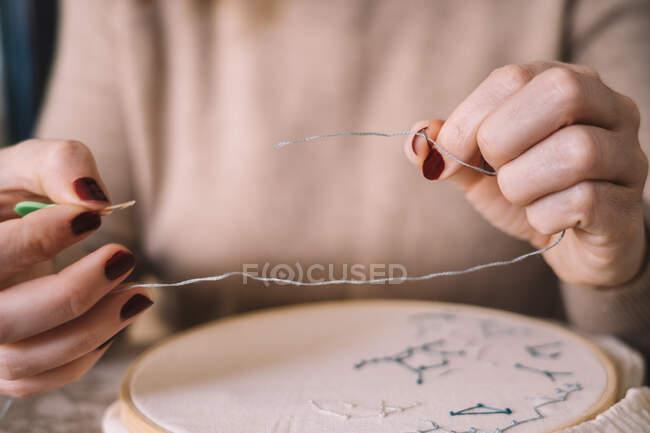 Crop fêmea anônima em roupa casual agulha de rosca para costurar o trabalho enquanto sentado à mesa em estúdio de luz — Fotografia de Stock