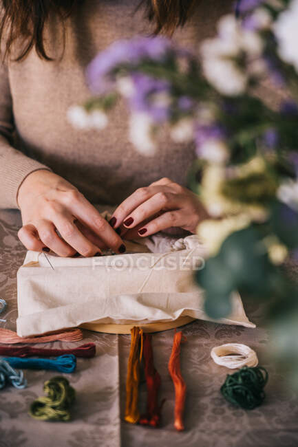 Front view of crop female with hoop and threads embroidering star constellations while sitting at table in light workshop — Stock Photo