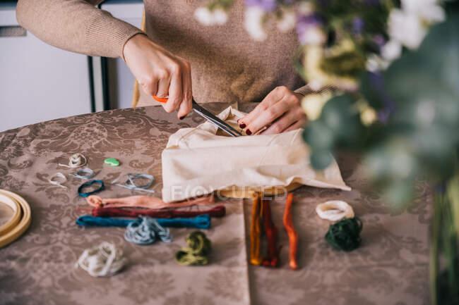 Cortar fios de corte feminino irreconhecíveis no tecido em aro ao fazer bordado e sentado na mesa com aro e fios — Fotografia de Stock