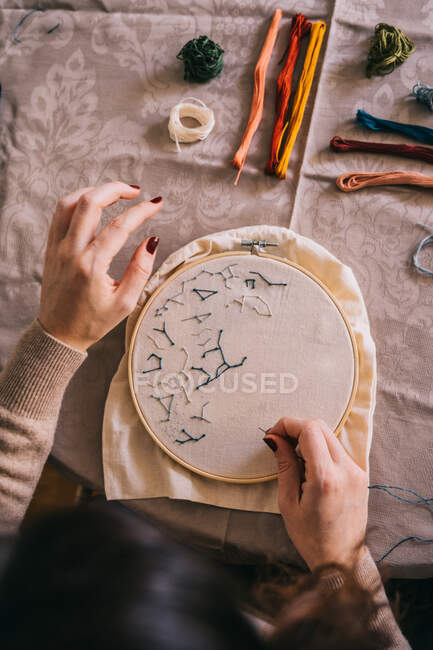 Top view crop female with hoop and threads embroidering star constellations while sitting at table in light workshop — Stock Photo