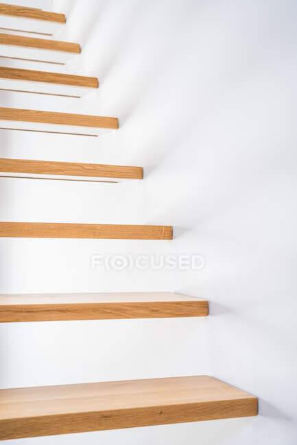 Wooden staircase above parquet near white wall with shadow in contemporary building in daylight — Stock Photo