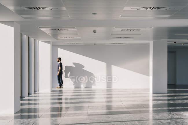 Бічний вид чоловіка стоїть біля вікна в порожньому коридорі з тінями і сонячним світлом на білих стінах і дивиться геть — стокове фото