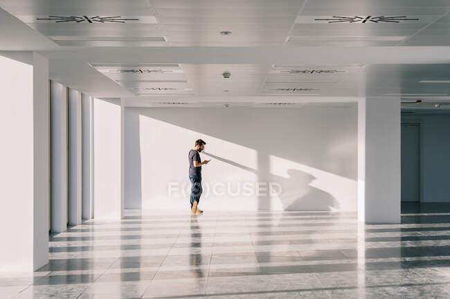 Бічний вид чоловіка стоїть у порожньому коридорі з білими стінами і творчими тінями при користуванні мобільним телефоном. — стокове фото