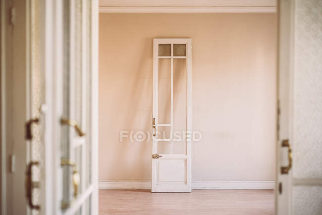 Old fashioned white wooden opened door with ornamental handles in retro style in empty apartment — Stock Photo