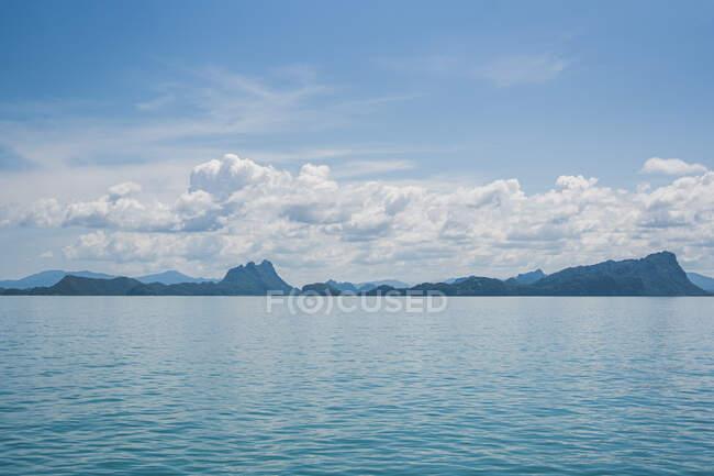 Pittoresca vista del fiume con acqua increspata contro i monti sotto il cielo nuvoloso blu alla luce del giorno — Foto stock