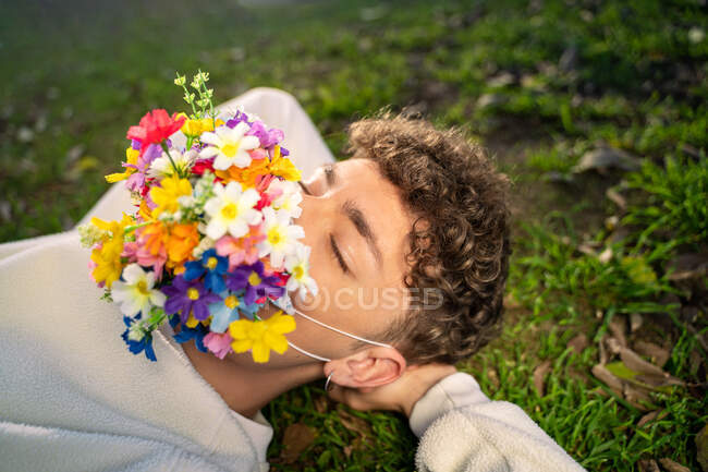 From above of anonymous young male with colorful blossoming flower mask on face and closed eyes lying on lawn in sunlight — Stock Photo