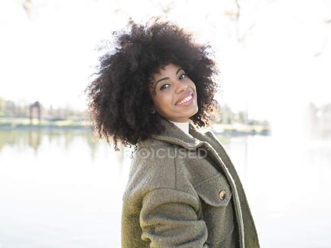 Весела молода афроамериканка з кучерявим волоссям в стильному теплому одязі посміхається і дивиться на камеру, відпочиваючи в парку біля озера в сонячний осінній день — стокове фото