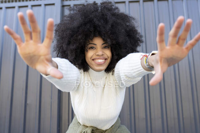Cheerful young African American lady with curly hair in casual clothes showing two hands and looking at camera on street — Stock Photo