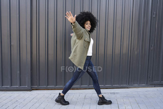 Side view of young happy African American female millennial with dark curly hair in trendy outfit walking on street with outstretched arms and looking at camera — Stock Photo