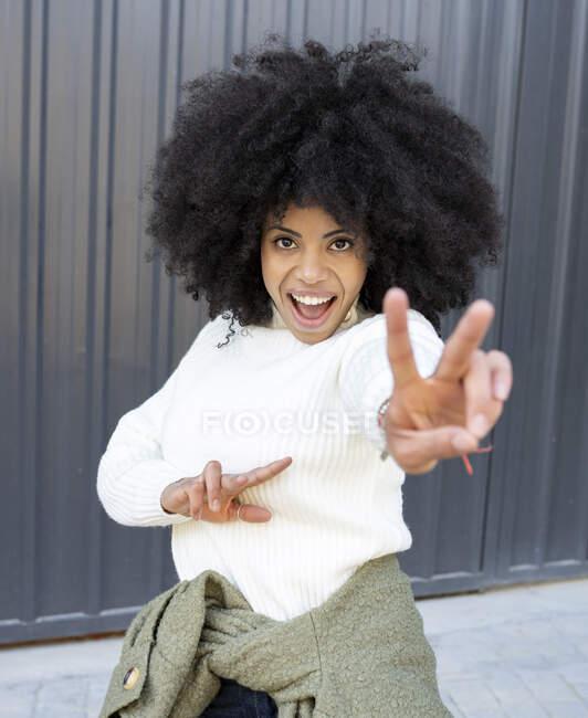 Allegro giovane signora afroamericana con i capelli ricci in abiti casual mostrando due dita segno con la bocca aperta e guardando la fotocamera sulla strada — Foto stock