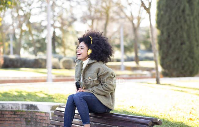 Зачарована молода афроамериканська жінка тисячоліття з кучерявим волоссям в стильному одязі, що відпочиває на лавці в парку і слухає улюблену пісню в навушниках — стокове фото
