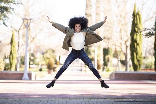 Полная длина веселой молодой этнической женщины с афроволосами в стильном наряде кричать и прыгать в парке в солнечный день — стоковое фото