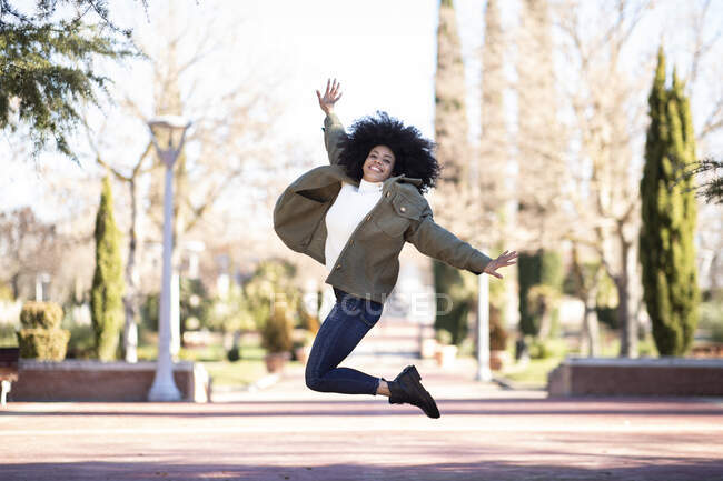 Full length of cheerful young ethnic woman with Afro hair in stylish outfit smiling and jumping in park on sunny day — Stock Photo