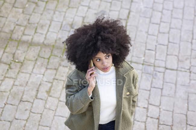 Angle élevé de concentré jeune afro-américaine millénium féminin avec les cheveux bouclés dans une tenue élégante ayant conversation téléphonique tout en marchant sur la rue pavée le jour ensoleillé — Photo de stock