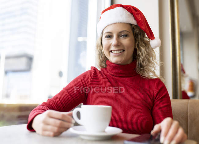 Deliziosa femmina in cappello Babbo Natale e dolcevita rosso seduta con tazza di caffè nel caffè e guardando la fotocamera durante le vacanze di Natale — Foto stock