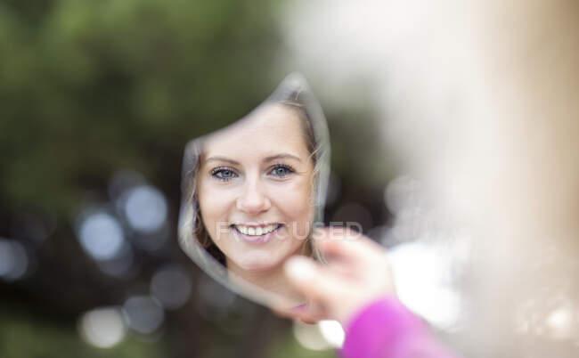 Mulher encantada refletindo em pedaço de espelho quebrado enquanto está na natureza e olhando para a câmera — Fotografia de Stock