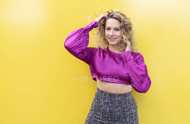 Mulher sorrindo vestindo roupas extravagantes tocando cabelo encaracolado loiro enquanto estava na rua no fundo amarelo e olhando para a câmera — Fotografia de Stock