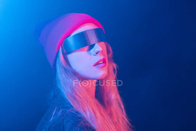 Trendy young female millennial with long blond hair in futuristic sunglasses adjusting hat while standing in dark room with neon illumination — Stock Photo