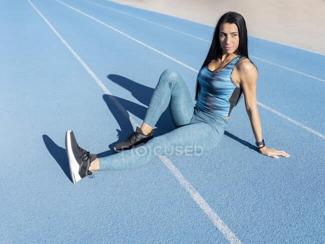 Высокий угол уверенной в себе спортсменки в спортивной одежде, сидящей на треке на стадионе во время тренировки и смотрящей в сторону — стоковое фото