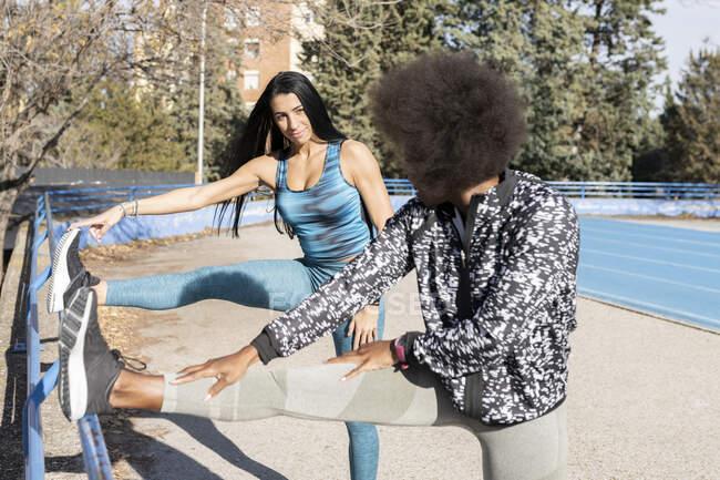 Різні бігуни в спортивній манері розтягують ноги і нагріваються перед тренуванням стоячи на стадіоні і дивлячись один на одного. — стокове фото