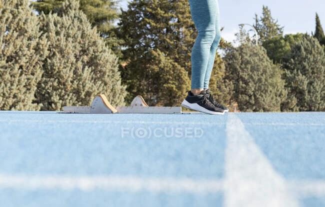 Ebenerdige Seitenansicht des Läufers, der in der Nähe der Startblöcke auf der Strecke steht und sich auf das Rennen im Stadion vorbereitet — Stockfoto