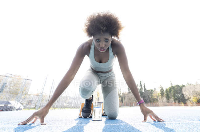 From below of African American female runner in starting blocks standing in crouch position while getting ready for sprint at stadium during workout — Stock Photo