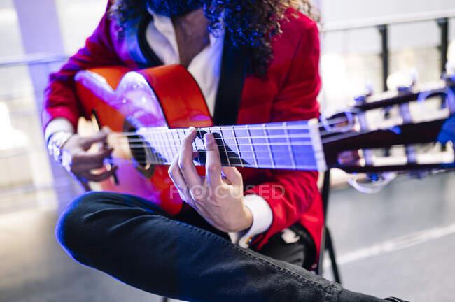 Crop uomo etnico con i capelli lunghi suonare la chitarra acustica durante le prove canzone sul palco alla luce dei riflettori — Foto stock