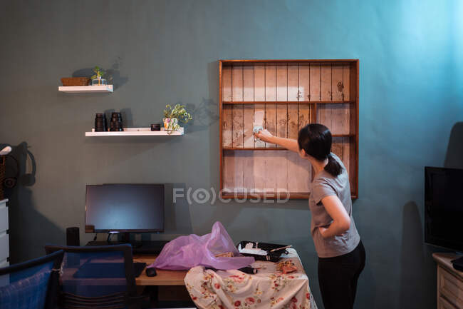 Side view of ethnic female with paintbrush painting wooden shelves in white color while renovating furniture — Stock Photo