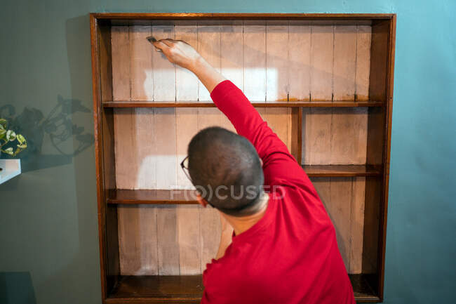 Back view male with paintbrush painting wooden shelves in white color while renovating furniture — Stock Photo