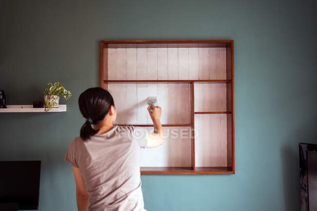 Back view ethnic female with paintbrush painting wooden shelves in white color while renovating furniture — Stock Photo