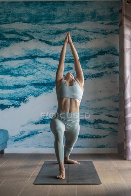Полное тело босых женщин, стоящих в положении Выпада полумесяца, растягивая тело и медитируя — стоковое фото